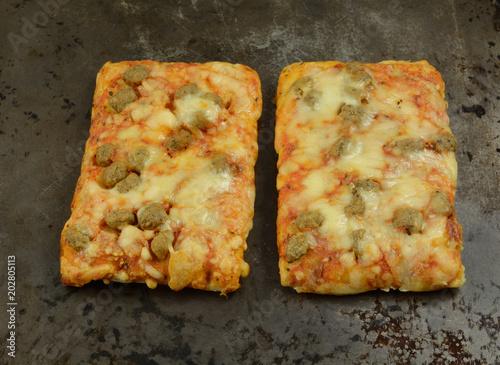 Valokuva  Rectangular sausage and cheese pizza pieces on on flatbread on weathered baking