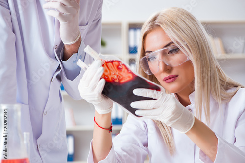 Fotografie, Obraz  Woman female doctor looking at blood samples in bag