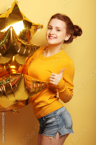 Photo  cute red girl standing in a studio, smiling widely and playing with gold balloons