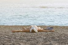 A Man Is Sunbathing On The Bea...