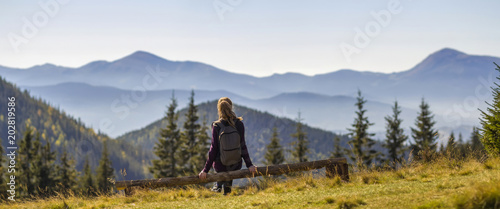 Photo  Back view of long-haired blond girl with backpack sitting on broken tree trunk enjoying breathtaking view of magnificent foggy Carpathian mountains, covered with ever-green forest on spring morning