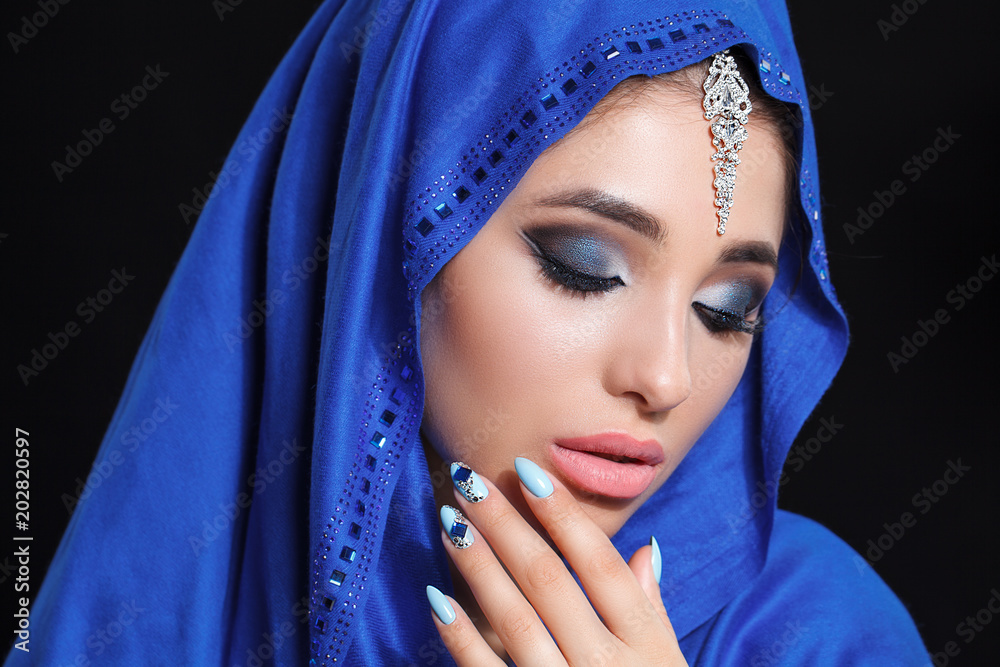 Fototapeta Gorgeous Young East Woman face portrait in hijab. Beauty Model Girl with bright eyebrows, perfect make-up, touching her face. Traditional. Isolated on black background. Smokey.Jewelry on her face