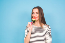 Beautiful Smiling Young Woman Holding Watermelon Slice On Stick On Blue Background With Copyspace