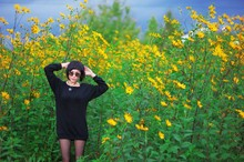 Young Cute Brunette Girl In Sunglasses And Black Tunic, Standing In Thickets Of Yellow Jerusalem Artichoke Flowers In Summer Sunny Day.