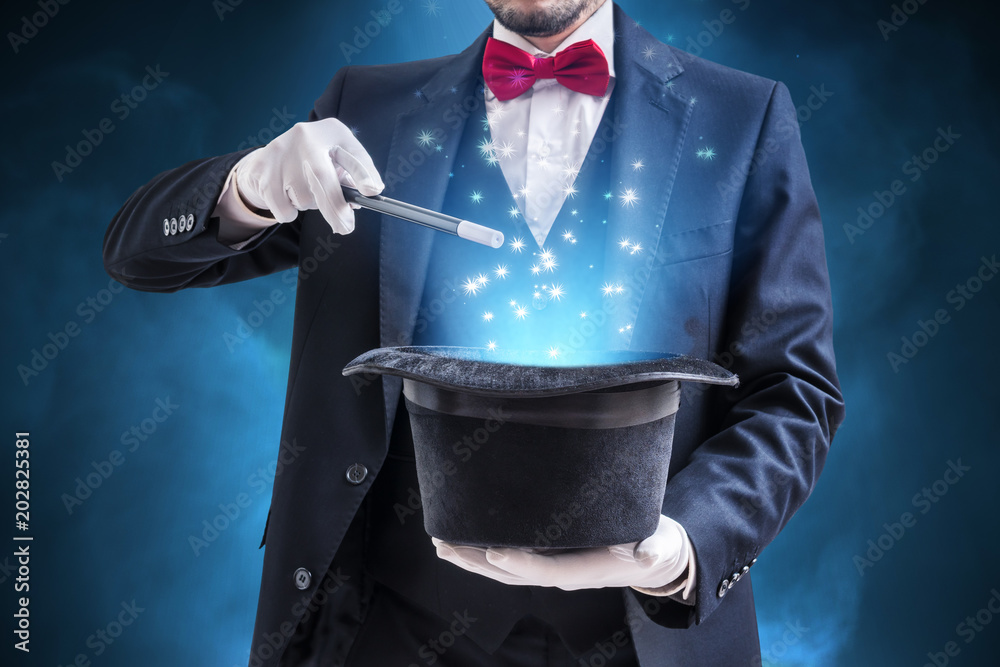 Fototapeta Magician or illusionist is showing magic trick. Blue stage light in background.