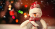 Snow falling against close-up of snowman on wooden table