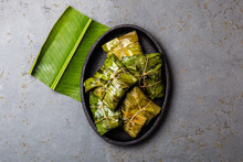 COLOMBIAN, CENTRAL AMERICAN FOOD. Tamales Wrapped In Banana Palm Tree Leaves On Black Plate, Gray Stone Background
