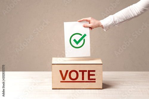 Papiers peints Pays d Afrique Close up of male hand putting vote into a ballot box, on grunge background