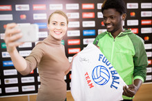 Portrait Of Smiling African-American Sportsman Taking Selfie With Fan And Holding Signed T-shirt