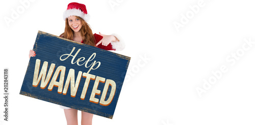 Christmas Help Wanted.Festive Redhead Smiling At Camera Holding Poster Against