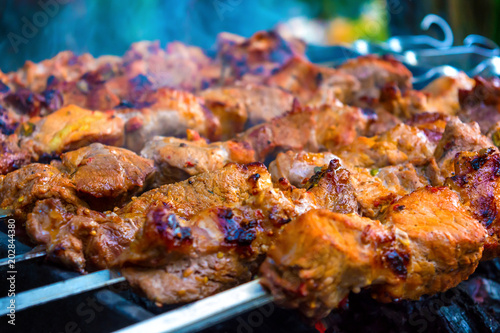 Poster Grill / Barbecue Photo of delicious pork barbecue fried on charcoal in the park