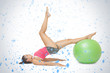 Attractive sporty brunette exercising with exercise ball against snow falling