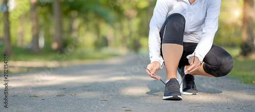 Fotografía  young fitness woman legs walking in the park outdoor, female runner running on the road outside, asian athlete jogging and exercise on footpath in sunlight morning