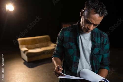 Photo  Actor reading their scripts on stage