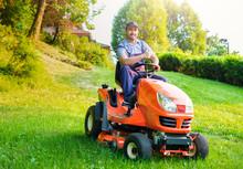 Gardener Driving A Riding Lawn...