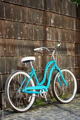 Papiers peints Velo Vintage turquoise bike with white elements standing near the brown wooden wall. Blue bicycle wood
