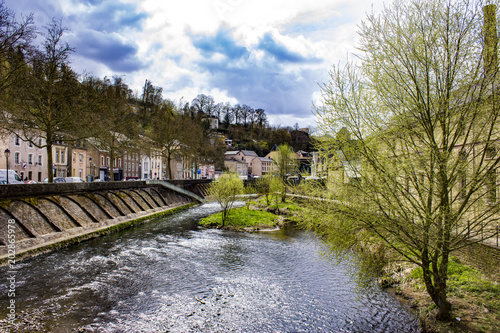 Fotografie, Obraz  Looking Down the Alzette River with Spring Trees Blooming on Each Side in Luxemb