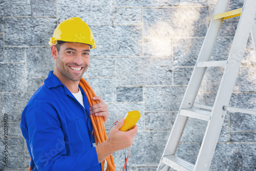 Poster  Smiling male electrician holding multimeter in office against grey