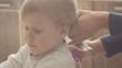 Mom makes the tail of her little daughter's hair, combs her hair to a little three-year-old girl, a girl with blond hair blond