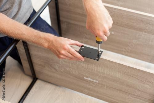 Fotografie, Tablou  Handyman folds a bookcase