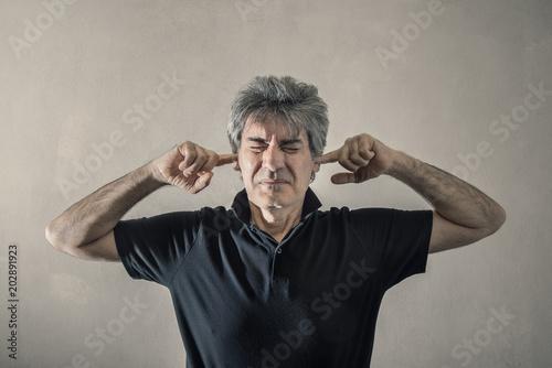 Fotografie, Obraz  uomo con le dita nelle orecchie per non sentire