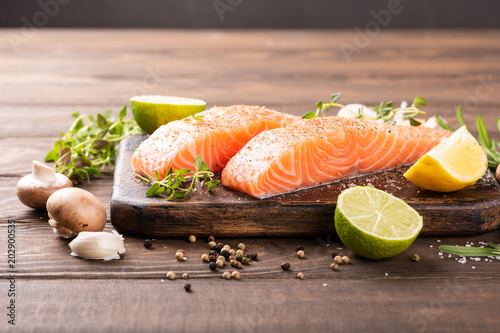 Fotografija Fresh raw salmon fillet with aromatic herbs, spices on old wooden background with copy space