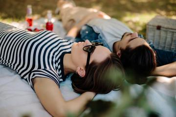Fototapeta Woman with boyfriend relaxing at picnic