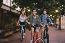 Young Friends Cycling In The City