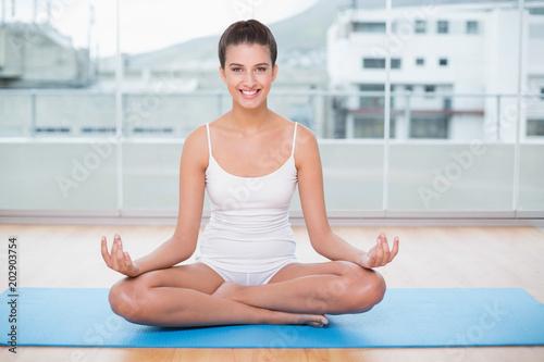 Fotobehang School de yoga Happy natural brown haired woman in white sportswear practicing yoga