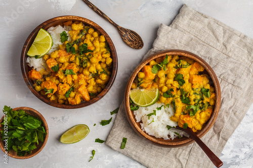 Photo Vegan Sweet Potato Chickpea curry in wooden bowl on light background, top view, copy space