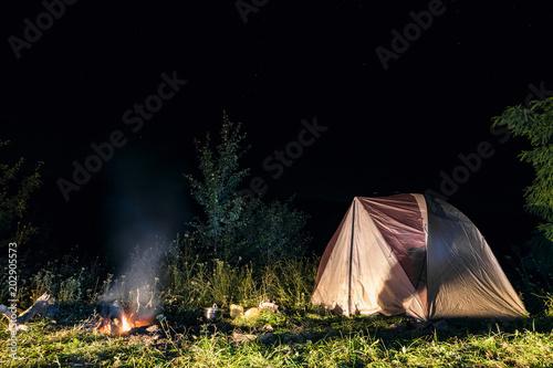 Foto op Aluminium Kamperen Tourist camping tent at night at a burning fire