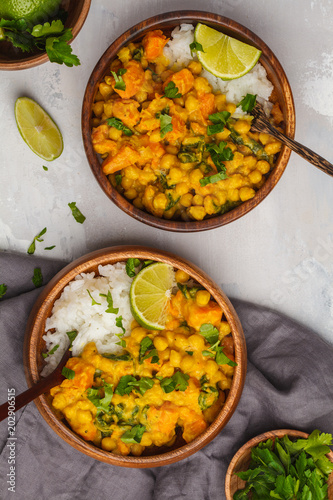 Vegan Sweet Potato Chickpea curry in wooden bowl on light background, top view, copy space. Healthy vegetarian food concept.