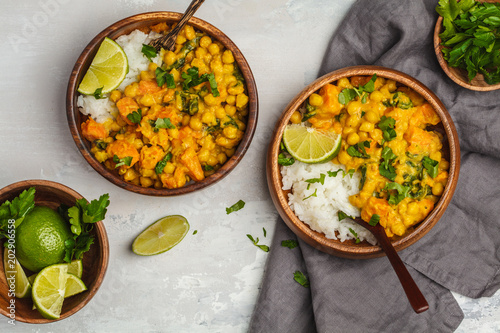 Valokuva  Vegan Sweet Potato Chickpea curry in wooden bowl on light background, top view, copy space