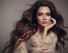 Beauty Fashion Brunette Portrait. Sexy Woman Wears In Stylish Fur Coat. Beautiful Girl Model With Evening Makeup, Long Healthy Curly Hair Style Posing Over Studio Gray Background.