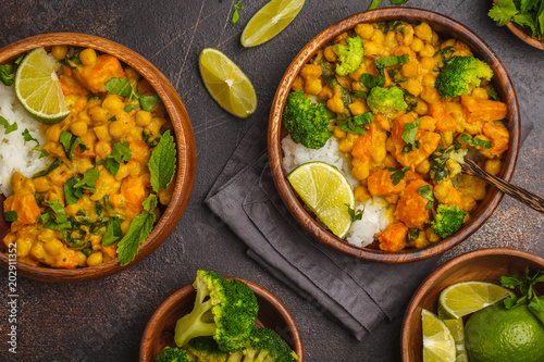 Vegan Sweet Potato Chickpea curry in wooden bowl on a dark background, top view. Healthy vegetarian food concept.