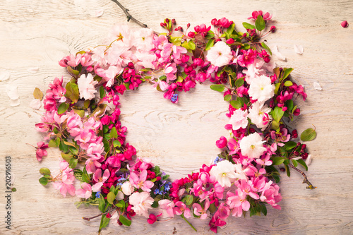 Heart shaped of flowers on wooden background