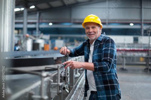 Obraz Portrait of smiling factory worker near production line - fototapety do salonu