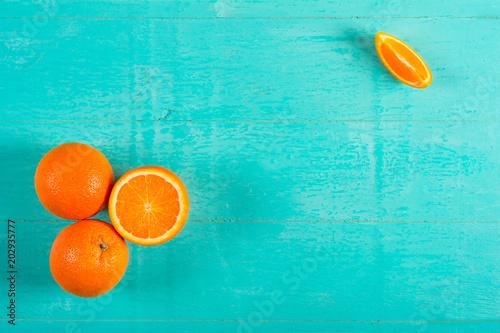 Fotografie, Obraz  Ripe juicy oranges on a blue wooden background