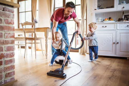 Father and two toddlers doing housework. Fototapet