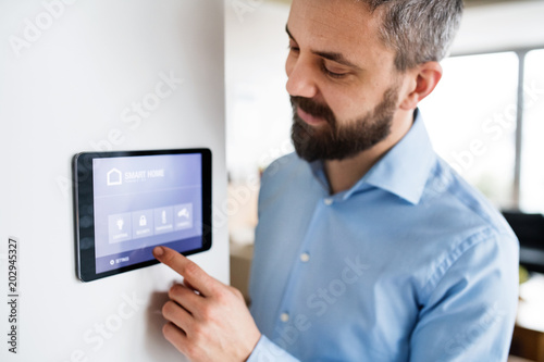 Cuadros en Lienzo A man pointing to a tablet with smart home screen at home.