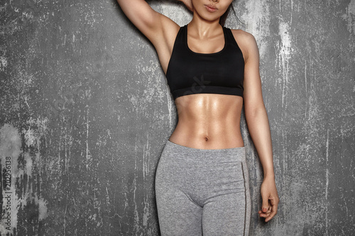 Fit Woman style with sexy hips. Female with perfect abdomen muscles. Beautiful Body in sport clothes near grey wall