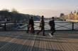 Blurry motion image of people walking on Pont des Arts bridge on Seine river in Paris.