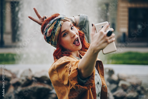 beautiful young woman taking selfie picture outdoors. hippie fashion blogger on vacation, taking self portrait with smartphone. street style, music festival portrait of authentic and fun young girl.