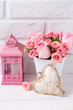 Pink roses flowers in white pot, decorative heart and pink lantern against white brick wall.
