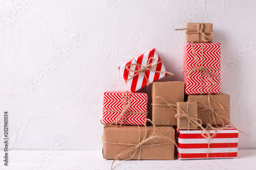 Wrapped colorful gift boxes with presents on white textured background.