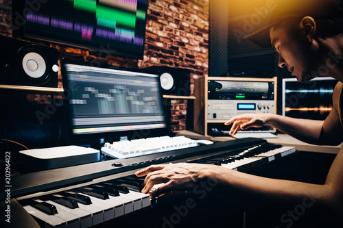 asian male music arranger hands composing song on midi piano & professional audio equipment in digital recording studio - 202964122