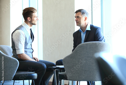 Fotografiet Mature businessman using a digital tablet to discuss information with a younger colleague in a modern business lounge
