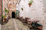 Fototapeta Uliczki - Small outdoor cafe in old style narrow street with brick walls, wooden furniture and cobbled stones.