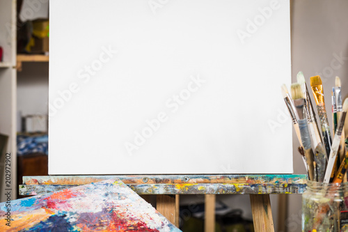 Art equipment: easel, brushes, tubes with paint, palette and paintings Wallpaper Mural