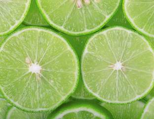 Green background with citrus fruit of lime slices.